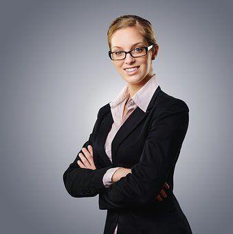 Fraue Oberkörper mit Brille und Anzug, strahlt souveränes Auftreten und positive Energie aus