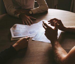 drei Menschen am Tisch bei einer Präsentation, Diskussion, Hände, Gestik