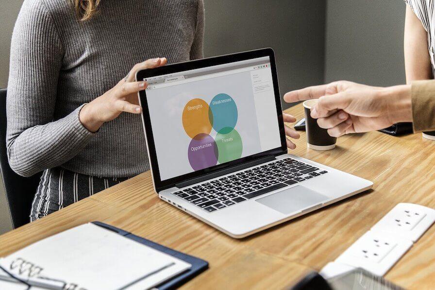 SWOT Unternehmensanalyse auf Laptop, Tisch, Zeigefinger, Frau mit grauem Oberteil
