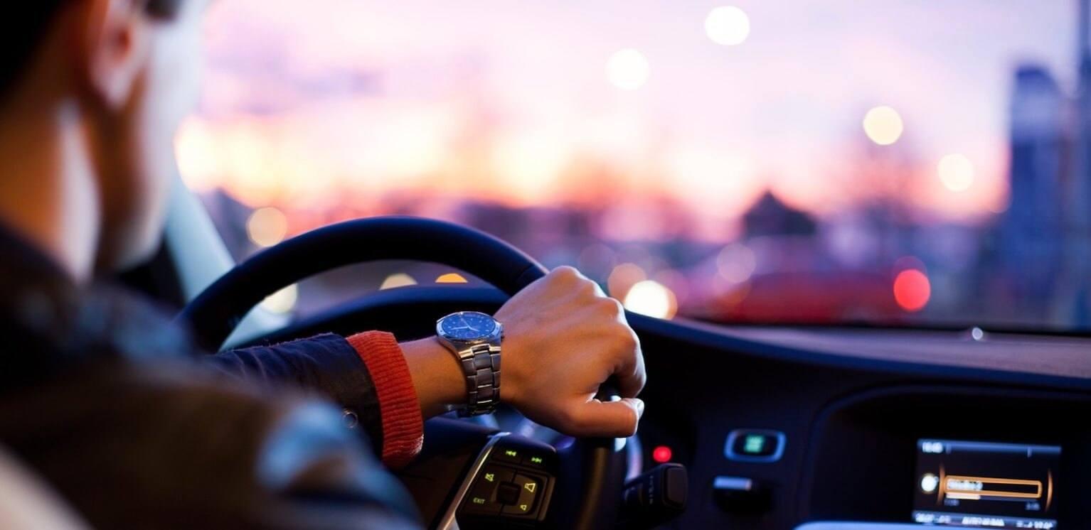 Persönlichkeitsbildung ist wie eine Autofahrt, Mann am Lenkrad mit Uhr und unscharfem Hintergrund