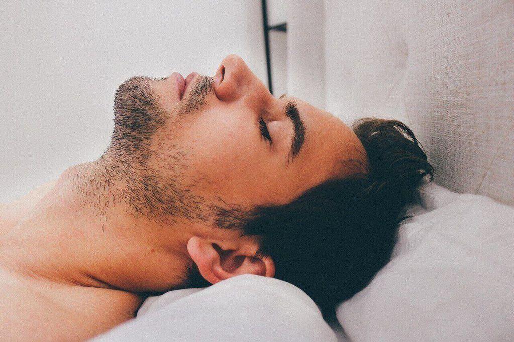 Mann liegt mit Kopf auf weißem Kissen, 7-9 Stunden Schlaf für ein gesundes persönliches Erscheinungsbild