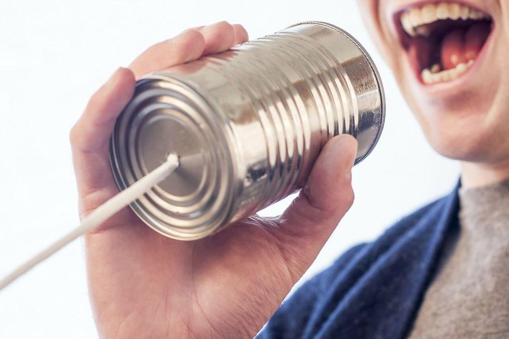 Persönliches Erscheinungsbild - Mann spricht in Dose mit Kabel