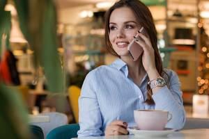 Eine Frau am Telefon im Cafe, sie ist ein Accountmanager