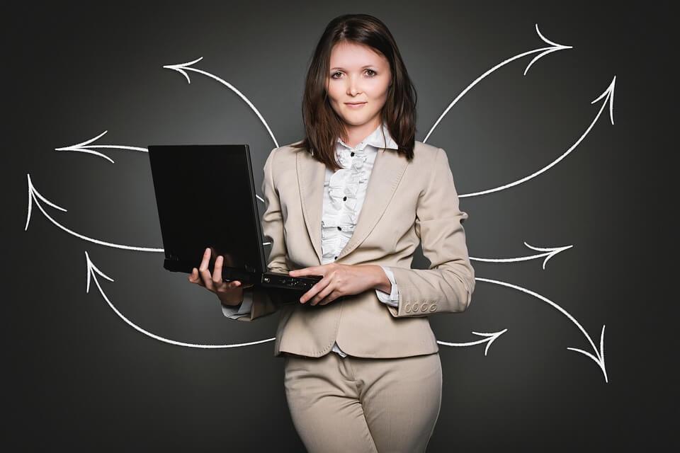 Eine Frau mit PC vor schwarzem Hintergrund. Mehrere Pfeile gehen hinter ihr zur Seite um ein Netzwerk darzustellen. Sie ist ein Accountmanager