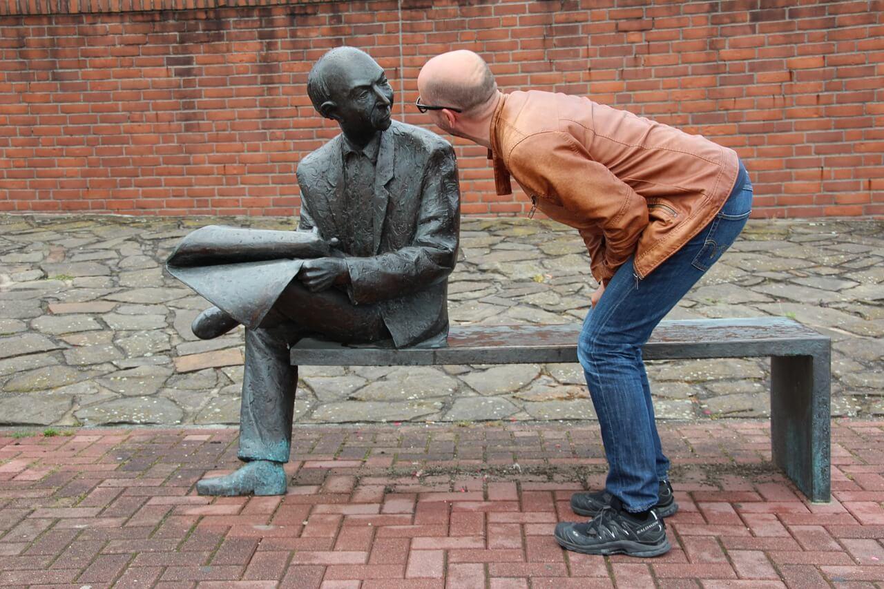 Kommunikationsprofi redet mit eiserner Statue, Scherzbild